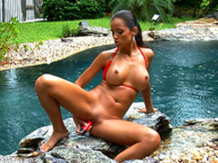 Brunette in bikini is masturbating outdoors