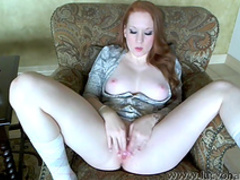 Slender redhead babe is playing with trimmed pussy