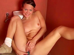 Smiling sweetie is playing with her dildo